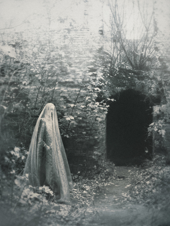 A veiled ghost in front of a cave.