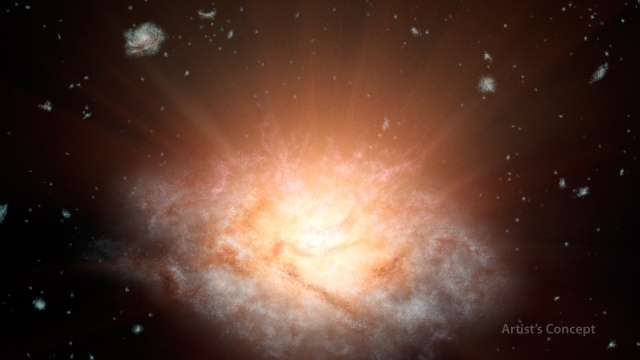 A huge galaxy shines brightly amidst smaller galaxies.